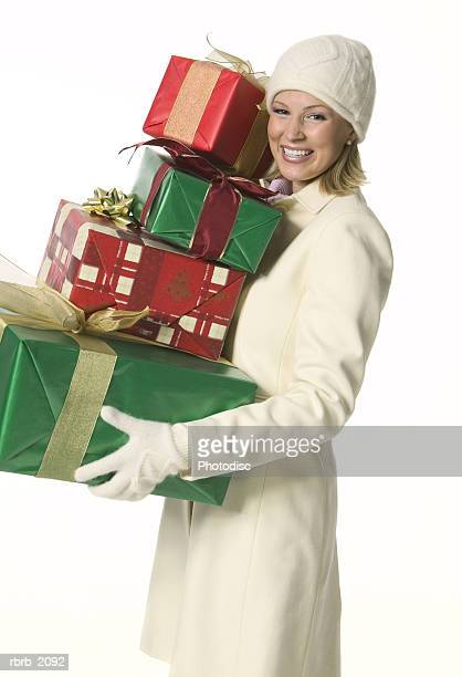 medium shot of a young adult woman in a winter outfit as she holds a stack of presents