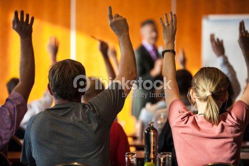 Los asistentes mostrando manos en un seminario : Foto de stock