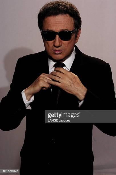 Meeting Michel Drucker Jeanpierre Foucault Photo studio plan de face de Michel DRUCKER lunettes noires rajustant son noeud de cravate