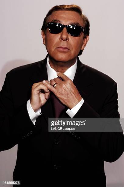 Meeting Michel Drucker Jeanpierre Foucault Photo studio plan de face de JeanPierre FOUCAULT lunettes noires rajustant son noeud de cravate