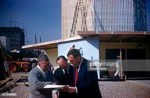 A meeting of planners and businessmen at an agricultural trade fair in Paris in the early nineteen sixties Huddled together around a set of plans the...