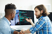 One of software developers pointing at computer screen while explaining his co-worker new method of data decoding