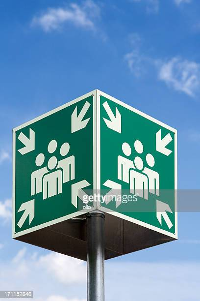 Meeting or evacuation point sign against blue sky