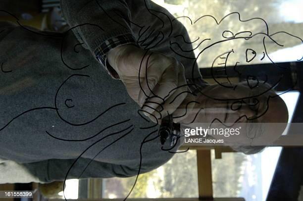 Meeting Wolinski Manara Attitude de Georges WOLINSKI dessinant une de ses héroïnes sur une vitre dans l'atelier de Milo MANARA à VERONE
