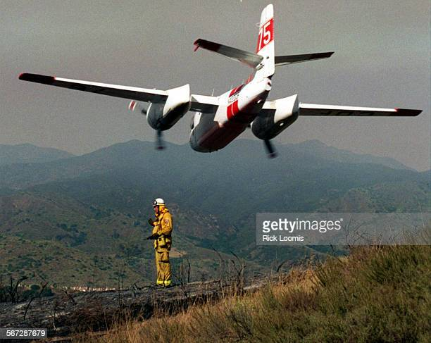 MEfireplane0529RL–Coto De Caza–An airplane with a load of fire retardant flies over OCFA Batallion Chief Gene Begnell as authorities work to...