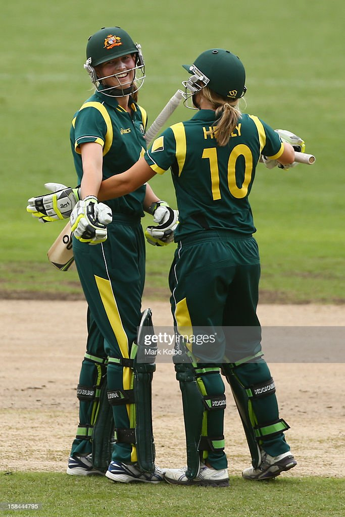 Meg Lanning of Australia celebrates scoring her century with Alyssa Healy of Australia during game three of the One Day International series between the Australian Southern Stars and New Zealand at North Sydney Oval on December 17, 2012 in Sydney, Australia.