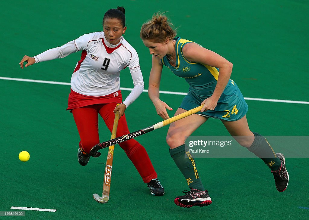 Meg Pearce of Australia and Nor Baini Hashim of Malaysian contest for the ball in the womens Australia under 21 v Malaysia game during day one of the 2012 International Super Series at Perth Hockey Stadium on November 22, 2012 in Perth, Australia.
