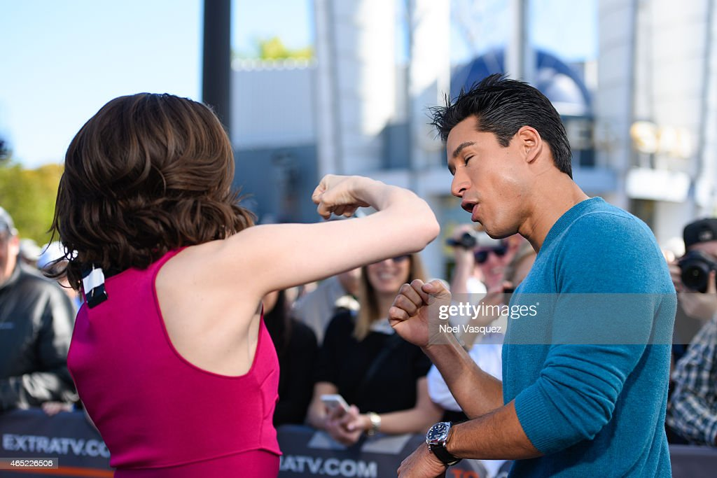 Megan Boone and Mario Lopez practice a stunt punch at 'Extra' at Universal Studios Hollywood on March 4, 2015 in Universal City, California.