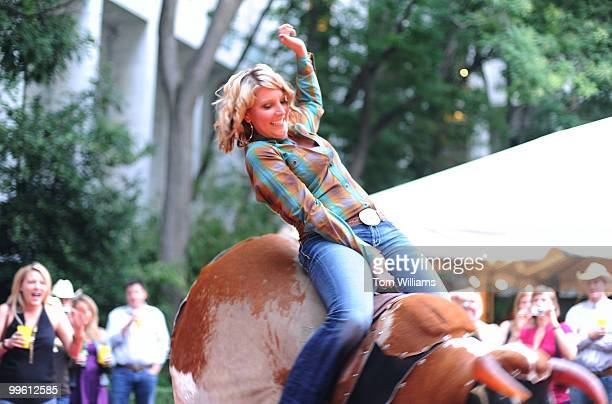 Megan Degenfelder from the office of Rep Cynthia Lummis RWyo rides a mechanical bull during the COWPIE Committee of Wyoming People in the East party...