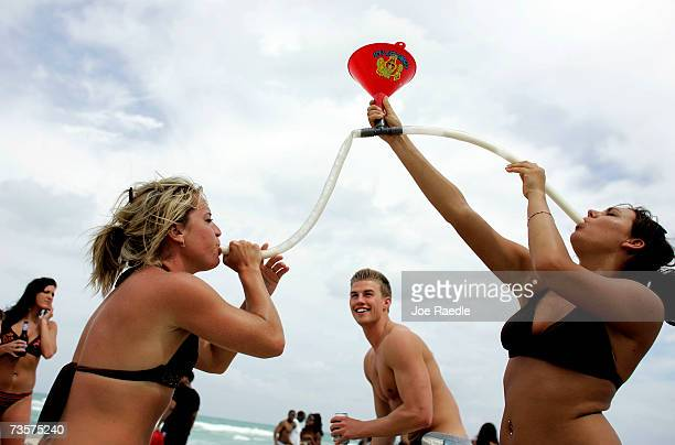 Megan Jump and Jenna Haring on spring break from Ball State University use a funnel to drink beer March 14 2007 on South Beach in Miami Beach Florida...