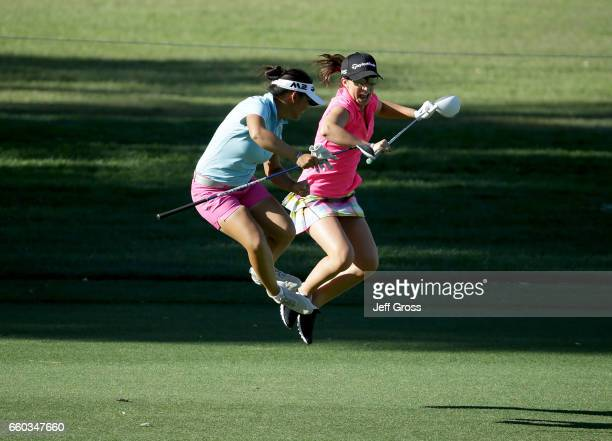 Megan Khang and amateur Victoria Arlen jump and share a laugh on the ninth fairway during a pro am at Mission Hills Country Club on March 29 2017 in...