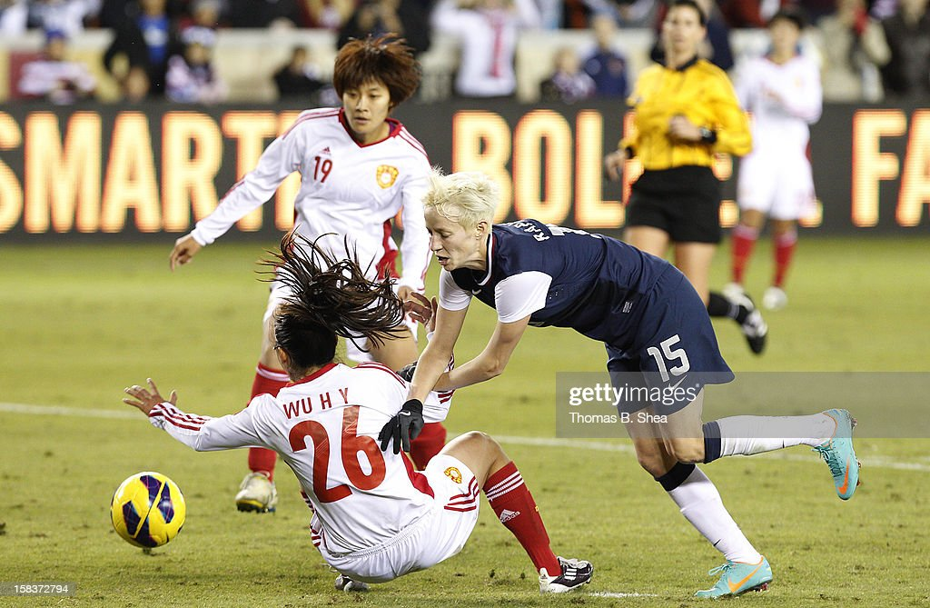 Megan Rapinoe #15 of the U.S. Women's National Team collides with Wu Haiyan defender #26 of the China Women's National Team and Pu Wei midfielder #11 of the China Women's National Team in an international friendly game at BBVA Compass Stadium on December 12, 2012 in Houston, Texas. USA won 4 to 0.