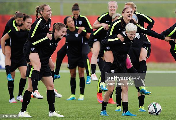 Megan Rapinoe of United States of America gives Alex Morgan of United States of America a piggy back during USA training at Waverly Soccer Complex on...