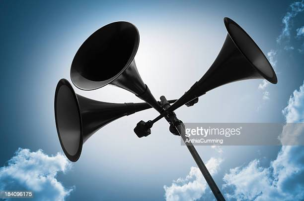 Megaphone loudspeakers silhouetted against blue sky
