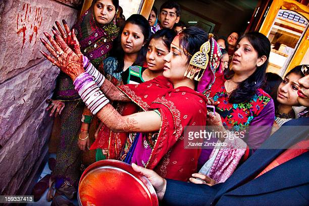 Megha the bride putting her hand colored with 'kumkum' on the exterior wall of her father's house leaving an imprint of her hand as a memory during...