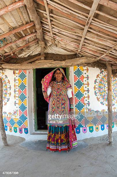Meghawal tribal woman standing in front of her family's ornately painted mud brick hut in Hodka a semiarid region bordering the Great Raan of Kutch...