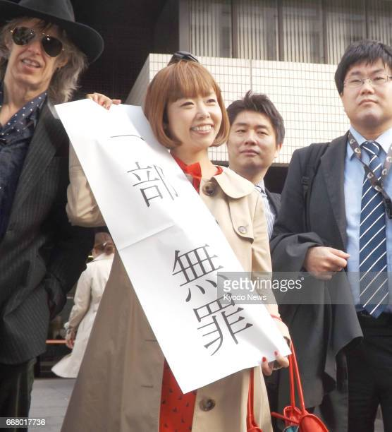 Megumi Igarashi a 45yearold artist who works under the pseudonym 'Rokudenashiko' holds up a sign in front of the Tokyo High Court on April 13 showing...