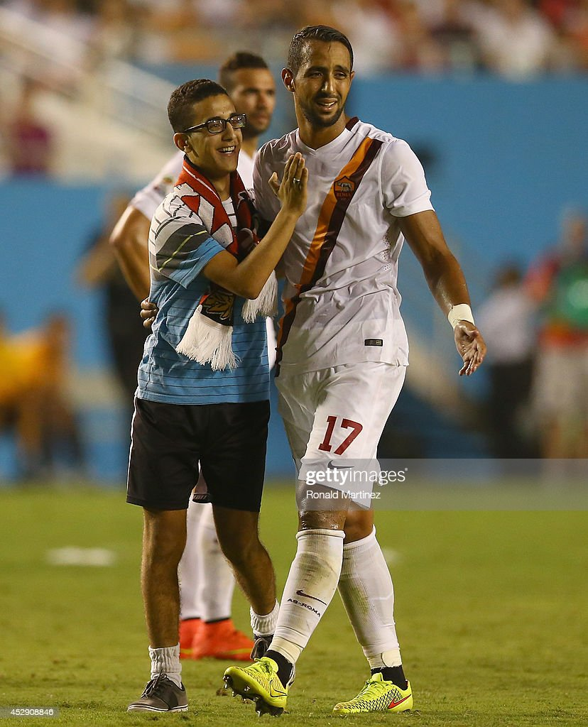 Mehdi Benatia #17 of AS Roma greets a fan, after fans disrupted the game against Real Madrid during a Guinness International Champions Cup 2014 game at Cotton Bowl on July 29, 2014 in Dallas, Texas.