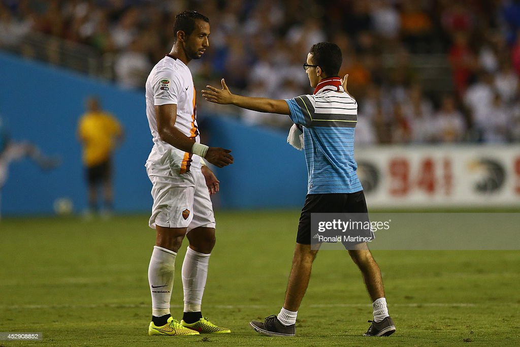 <a gi-track='captionPersonalityLinkClicked' href=/galleries/search?phrase=Mehdi+Benatia&family=editorial&specificpeople=778655 ng-click='$event.stopPropagation()'>Mehdi Benatia</a> #17 of AS Roma greets a fan, after fans disrupted the game against Real Madrid during a Guinness International Champions Cup 2014 game at Cotton Bowl on July 29, 2014 in Dallas, Texas.