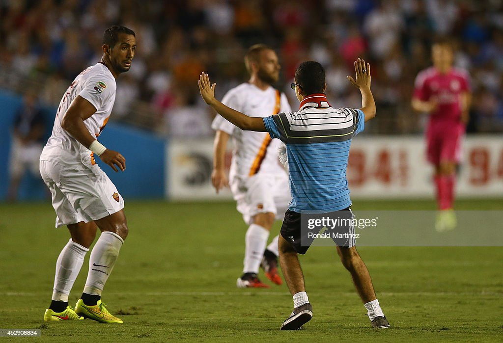 <a gi-track='captionPersonalityLinkClicked' href=/galleries/search?phrase=Mehdi+Benatia&family=editorial&specificpeople=778655 ng-click='$event.stopPropagation()'>Mehdi Benatia</a> #17 of AS Roma is suprised by a fan, after fans disrupted the game against Real Madrid during a Guinness International Champions Cup 2014 game at Cotton Bowl on July 29, 2014 in Dallas, Texas.