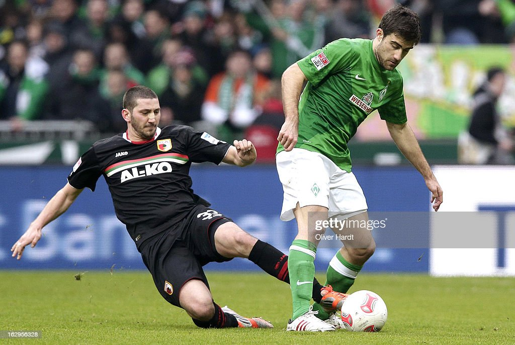 Mehmet Ekici (R) of Bremen and Sascha Moelders (L) of Augsburg battle for the ball during the Bundesliga match between SV Werder Bremen and FC Augsburg at Weser Stadium on March 2, 2013 in Bremen, Germany.