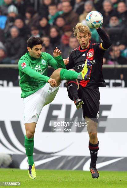 Mehmet Ekici of Bremen and Simon Rolfes of Leverkusen battle for the ball during the Bundesliga match between SV Werder Bremen and Bayer 04...
