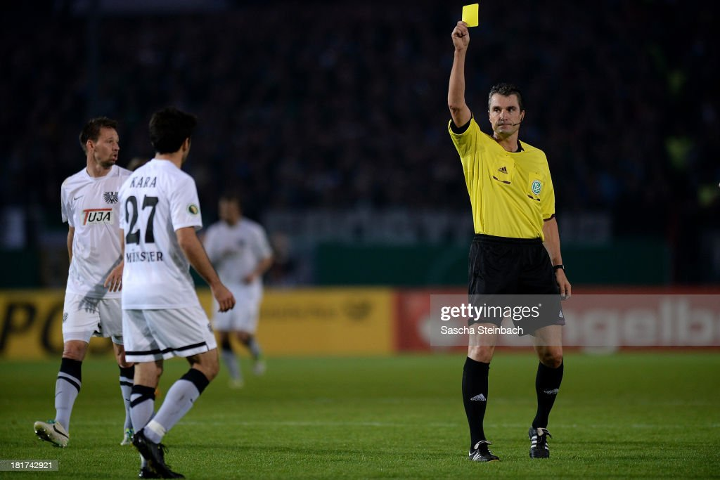 Mehmet Kara of Muenster is shown a yellow card by referee <a gi-track='captionPersonalityLinkClicked' href=/galleries/search?phrase=Knut+Kircher&family=editorial&specificpeople=645627 ng-click='$event.stopPropagation()'>Knut Kircher</a> during DFB Cup second round match between Preussen Muenster and FC Augsburg at Preussenstadion on September 24, 2013 in Muenster, Germany.