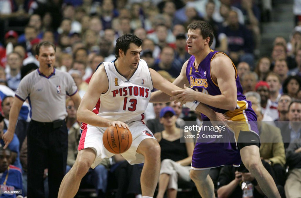 Mehmet Okur #13 of the Detroit Pistons dribbles on Slava Medvedenko #14 of the Los Angeles Lakers during game three of the 2004 NBA Finals June 10, 2004 at the Palace of Auburn Hills, in Auburn Hills Michigan.
