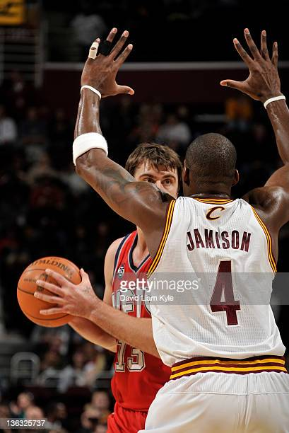 Mehmet Okur of the New Jersey Nets looks to pass the ball defended by Antawn Jamison of the Cleveland Cavaliers at The Quicken Loans Arena on January...