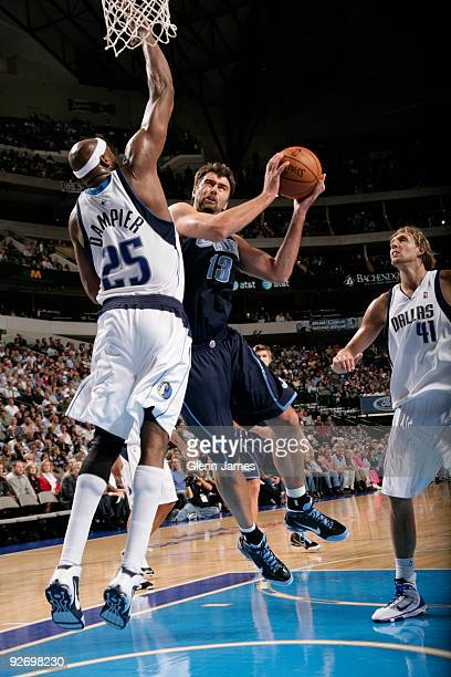 Mehmet Okur of the Utah Jazz goes up for the layup in the lane against Erick Dampier of the Dallas Mavericks during a game at the American Airlines...