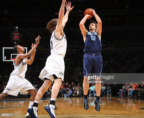 Mehmet Okur of the Utah Jazz shoots against Fabricio Oberto and Nick Young of the Washington Wizards at the Verizon Center on March 27 2010 in...