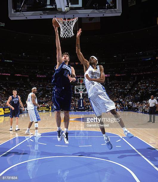 Mehmet Okur of the Utah Jazz shoots past Marcus Camby of the Denver Nuggets during the game at the Pepsi Center on November 6 2004 in Denver Colorado...