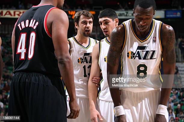 Mehmet Okur of the Utah Jazz talks with teammate Enes Kanter during foul shots taken by teammate Josh Howard against the Portland Trail Blazers...