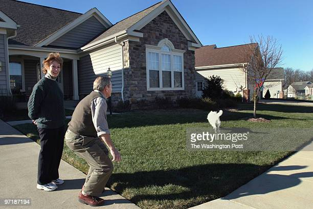 Lynn and Bob Levvis play with their dog Snowball at their home in Heritage Hunt The upscale development has a golf course and a wide range of...