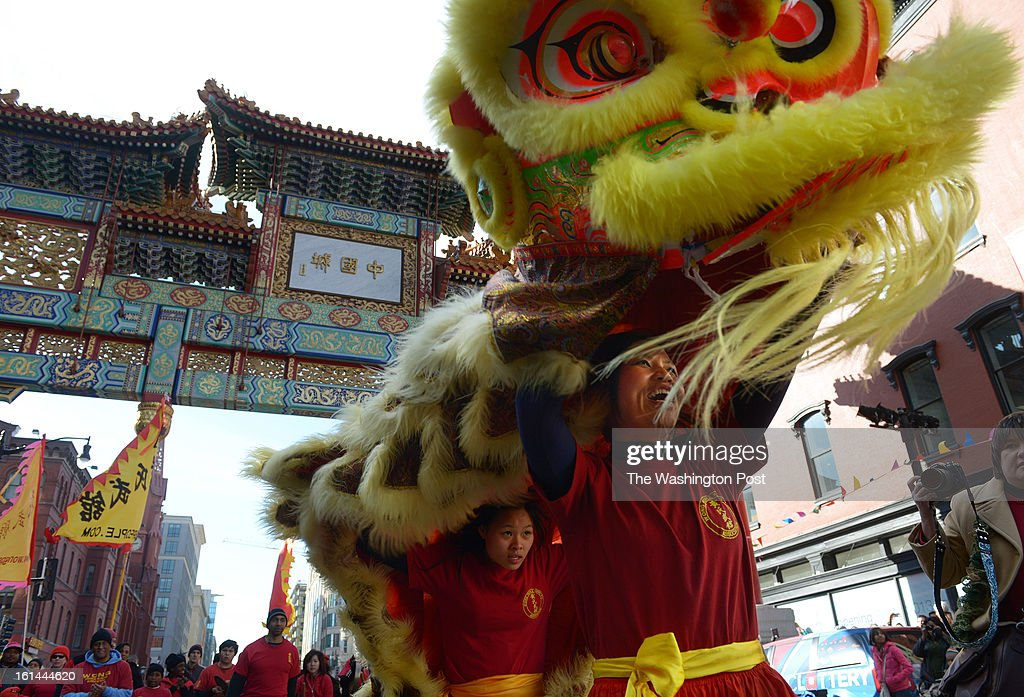 Mei Cao, right, takes part in a lion dance with other members of the Wong People Kung Fu Association during a parade to celebrate the Chinese New Year on Sunday February 10, 2013 in Washington, DC. Scores of people turned out for the event that ushers in the year of the Snake.