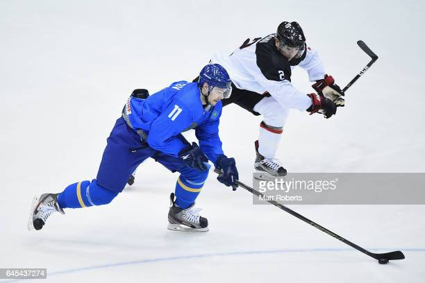 Mei Ushu of Japan and Ilya Kovzalov of Kazakhstan battle for the puck in the men's ice hockey match between Japan and Kazakhstan on day nine of the...