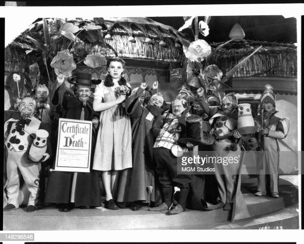 Meinhart Raabe holding a death certificate and Judy Garland surrounded by munchkins in a scene from the film 'The Wizard Of Oz' 1939