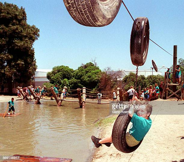 MEKids/Tire swing0723GK–Ryan Bena age 5 rides the tire swing at Adventure Playground Huntington BeachThe Playground features a rope bridge the mud...