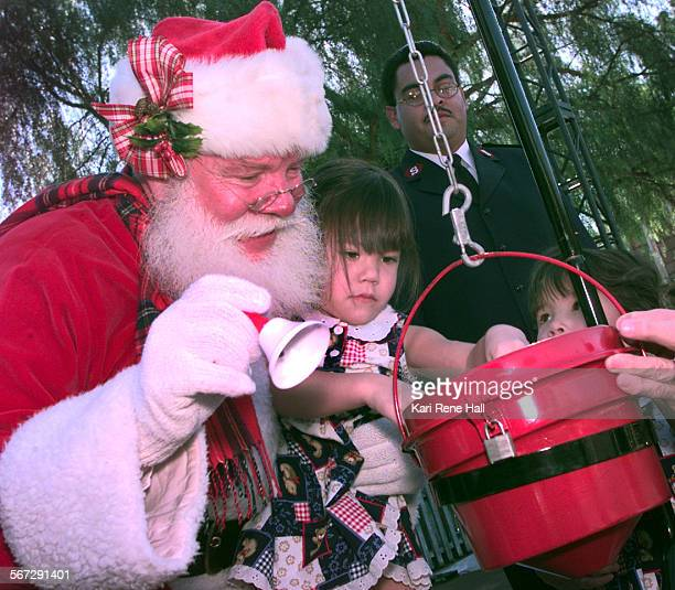 MEKnottssalvationD112098KRH––Santa Claus played by Harry Winters lifts up Justine Stewart of Valinda so that she can put a dollar in the Salvation...