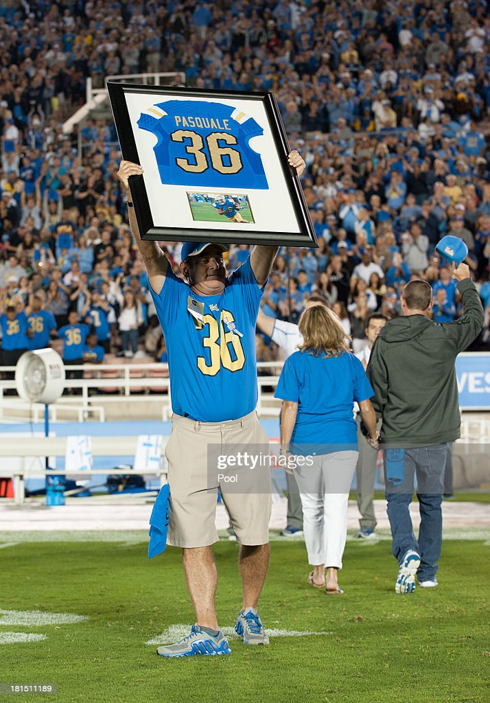 Mel Pasquale holds up the framed jersey of his son Nick Pasquale #36 as the UCLA Bruins honor his memory during the first quarter break against the New Mexico State Aggies at the Rose Bowl on September 21, 2013 in Pasadena, California.