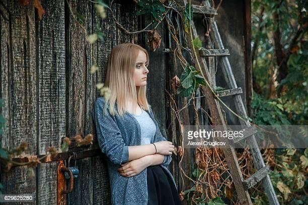 Melancholic blonde woman leaning at wooden barn door