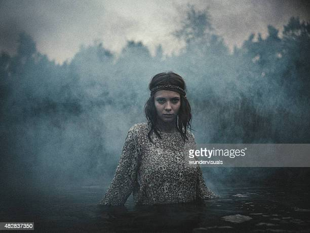 Melancholy girl standing in a lake surrounded by smoke