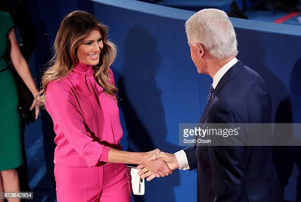 Melania Trump shakes hands with former US President Bill Clinton before the town hall debate at Washington University on October 9 2016 in St Louis...