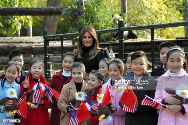 Melania Trump wife of US President Donald Trump poses for photographs with a giant panda and local children at Beijing Zoo on November 10 2017 in...