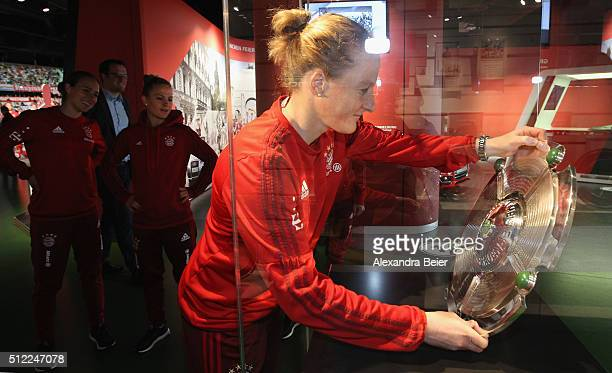 Melanie Behringer of FC Bayern Muenchen hands over the 2015 Women's German Champioship trophy to the FCB Erlebniswelt club museum as her teammates...
