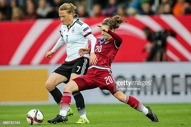 Melanie Behringer of Germany is challenged by Margarita Chernomyrdina of Russia during the UEFA Women's Euro 2017 Qualifier match between Germany and...