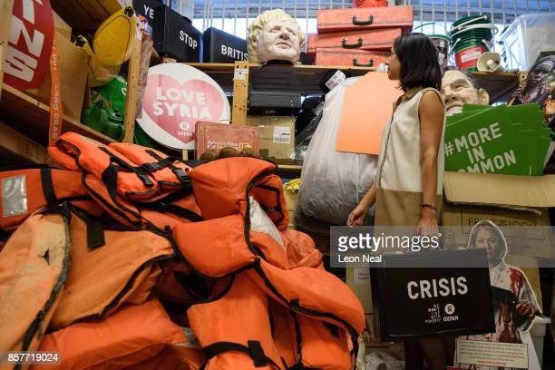 Melanie Kramers of Oxfam holds a 'Crisis' briefcase while surrounded by assorted props used in political campaigns in the store room at Oxfam's...