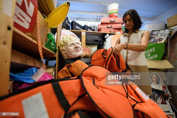 Melanie Kramers of Oxfam holds a life jacket previously used by a refugee while surrounded by assorted props used in political campaigns in the store...
