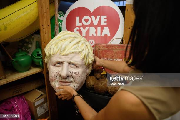 Melanie Kramers of Oxfam holds a mask of Foreign Secretary Boris Johnson while surrounded by assorted props used in political campaigns in the store...
