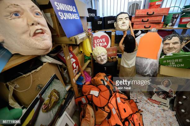 Melanie Kramers of Oxfam holds a mask of former Chancellor George Osborne while surrounded by assorted props used in political campaigns in the store...